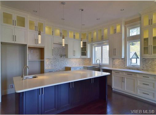 view of kitchen fr. side of island eating chairs  -